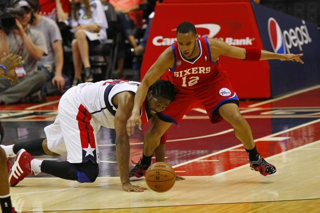 Apr 12, 2013; Washington, DC, USA; Philadelphia 76ers small forward Evan Turner (12) and Washington Wizards center Nene (42) battle for the ball in the third quarter at Verizon Center. The 76ers won 97-86. Mandatory Credit: Geoff Burke-USA TODAY Sports
