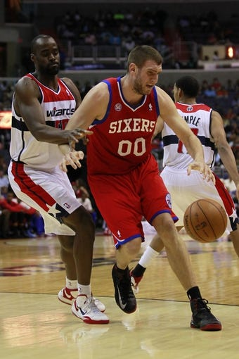 Apr 12, 2013; Washington, DC, USA; Philadelphia 76ers center Spencer Hawes (00) dribbles the ball as Washington Wizards center Emeka Okafor (50) defends in the third quarter at Verizon Center. The 76ers won 97-86. Mandatory Credit: Geoff Burke-USA TODAY Sports