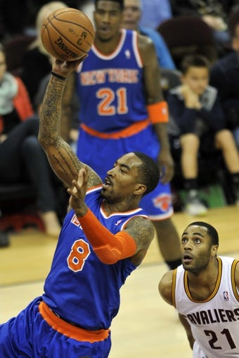 Apr 12, 2013; Cleveland, OH, USA; New York Knicks shooting guard J.R. Smith (8) drives to the basket past Cleveland Cavaliers shooting guard Wayne Ellington (21) in the second quarter at Quicken Loans Arena. Mandatory Credit: David Richard-USA TODAY Sports