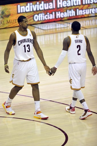Apr 12, 2013; Cleveland, OH, USA; Cleveland Cavaliers power forward Tristan Thompson (13) celebrates a basket with point guard Kyrie Irving (2) in the second quarter at Quicken Loans Arena. Mandatory Credit: David Richard-USA TODAY Sports