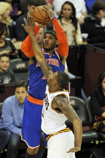Apr 12, 2013; Cleveland, OH, USA; New York Knicks small forward Carmelo Anthony (7) is fouled by Cleveland Cavaliers small forward Alonzo Gee (33) while attempting a three-point basket in the third quarter at Quicken Loans Arena. Mandatory Credit: David Richard-USA TODAY Sports