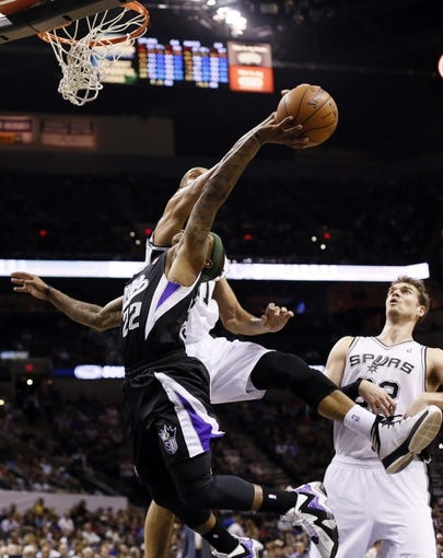 Apr 12, 2013; San Antonio, TX, USA; Sacramento Kings guard Isaiah Thomas (22) has his shot blocked by San Antonio Spurs forward Tim Duncan (behind) during the second half at the AT&T Center. The Spurs won 108-101. Mandatory Credit: Soobum Im-USA TODAY Sports