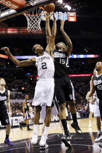 Apr 12, 2013; San Antonio, TX, USA; Sacramento Kings center DeMarcus Cousins (15) shoots while being defended by San Antonio Spurs forward Kawhi Leonard (2) during the second half at the AT&T Center. The Spurs won 108-101. Mandatory Credit: Soobum Im-USA TODAY Sports