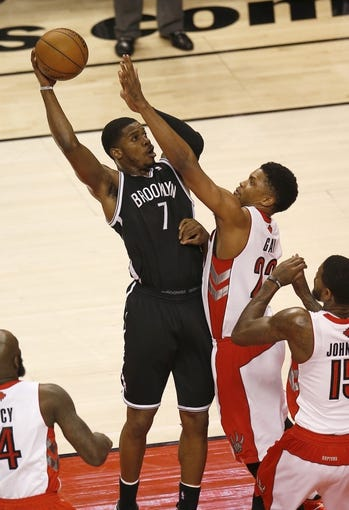 Apr 14, 2013; Toronto, ON, Canada; Brooklyn Nets guard Joe Johnson (7) scores against Toronto Raptors forward Rudy Gay (22) at the Air Canada Centre. Mandatory Credit: Tom Szczerbowski-USA TODAY Sports