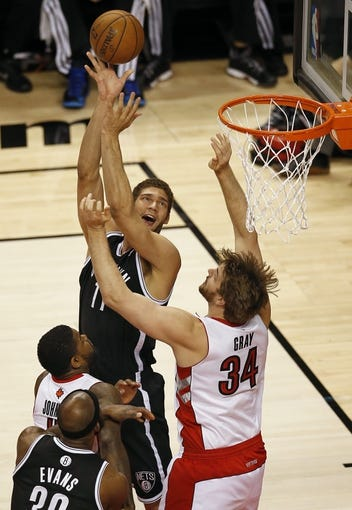 Apr 14, 2013; Toronto, ON, Canada; Brooklyn Nets center Brook Lopez (11) scores against Toronto Raptors center Aaron Gray (34) at the Air Canada Centre. Mandatory Credit: Tom Szczerbowski-USA TODAY Sports