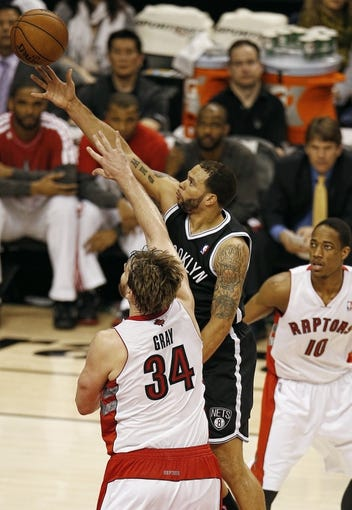 Apr 14, 2013; Toronto, ON, Canada; Brooklyn Nets point guard Deron Williams (8) scores a basket over Toronto Raptors center Aaron Gray (34) at the Air Canada Centre. The Raptors beat the Nets 93-87. Mandatory Credit: Tom Szczerbowski-USA TODAY Sports