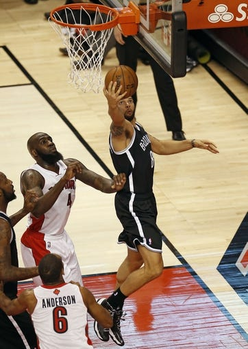 Apr 14, 2013; Toronto, ON, Canada; Brooklyn Nets point guard Deron Williams (8) scores a basket against Toronto Raptors forward Quincy Acy (4) at the Air Canada Centre. The Raptors beat the Nets 93-87. Mandatory Credit: Tom Szczerbowski-USA TODAY Sports