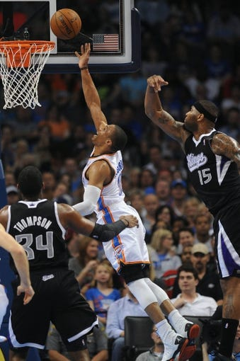 Apr 15, 2013; Oklahoma City, OK, USA; Oklahoma City Thunder guard Russell Westbrook (0) attempts a shot against Sacramento Kings center DeMarcus Cousins (15) and Kings forward Jason Thompson (34) during the second half at Chesapeake Energy Arena. Mandatory Credit: Mark D. Smith-USA TODAY Sports