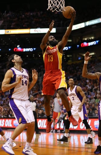 Apr. 15, 2013; Phoenix, AZ, USA: Houston Rockets guard James Harden (13) drives to the basket against Phoenix Suns forward Luis Scola (14) in the first quarter at the US Airways Center. Mandatory Credit: Mark J. Rebilas-USA TODAY Sports
