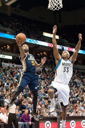 Apr 15, 2013; Minneapolis, MN, USA; Utah Jazz point guard Mo Williams (5) shoots and Minnesota Timberwolves power forward Dante Cunningham (33) defends in the fourth quarter at Target Center. The Jazz won 96-80. Mandatory Credit:  Greg Smith-USA TODAY Sports