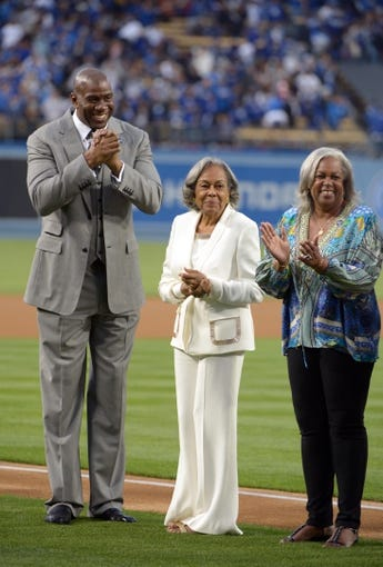 Apr 15, 2013; Los Angeles, CA, USA; Los Angeles Dodgers co-owner Magic Johnson (left) with the late Jackie Robinson's wife Rachel Robinson (center) and daughter Sharon Robinson attend the game against the San Diego Padres at Dodger Stadium. Mandatory Credit: Kirby Lee-USA TODAY Sports