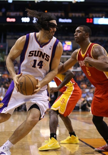 Apr. 15, 2013; Phoenix, AZ, USA: The hair of Phoenix Suns forward Luis Scola (14) flies into his face as he drives to the basket against Houston Rockets forward Terrence Jones (6) in the second half at the US Airways Center. The Suns defeated the Rockets 119-112. Mandatory Credit: Mark J. Rebilas-USA TODAY Sports