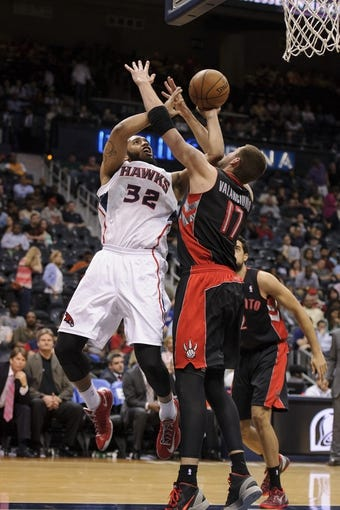 Apr 16, 2013; Atlanta, GA, USA; Atlanta Hawks power forward Mike Scott (32) is fouled by Toronto Raptors center Jonas Valanciunas (17) as he drives to the basket during the second half at Philips Arena. The Raptors won 113-96. Mandatory Credit: Paul Abell-USA TODAY Sports