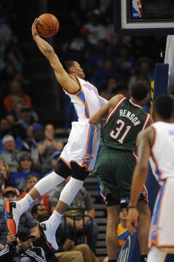 Apr 17, 2013; Oklahoma City, OK, USA; Oklahoma City Thunder guard Russell Westbrook (0) attempts a dunk against Milwaukee Bucks center John Henson (31) during the first half at Chesapeake Energy Arena. Mandatory Credit: Mark D. Smith-USA TODAY Sports