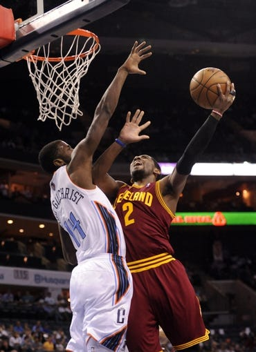 April 17, 2013; Charlotte, NC, USA; Cleveland Cavaliers guard Kyrie Irving (2) drives to the basket and scores as he is defended by Charlotte Bobcats forward Michael Kidd-Gilchrist (14) during the game at Time Warner Cable Arena. Mandatory Credit: Sam Sharpe-USA TODAY Sports