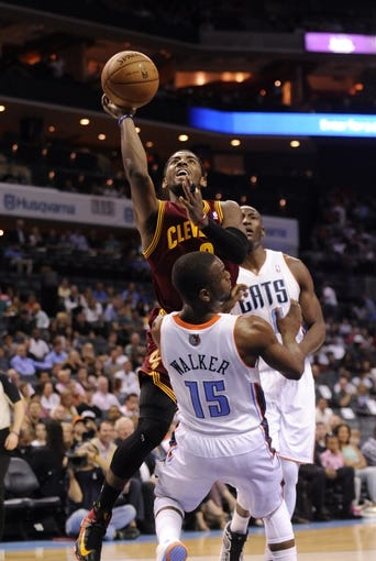 April 17, 2013; Charlotte, NC, USA; Cleveland Cavaliers guard Kyrie Irving (2) drives into Charlotte Bobcats guard Kemba Walker (15) as he goes to the basket during the game at Time Warner Cable Arena. Mandatory Credit: Sam Sharpe-USA TODAY Sports