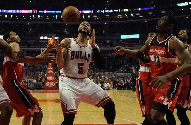 Apr 17, 2013; Chicago, IL, USA; Chicago Bulls power forward Carlos Boozer (5), Washington Wizards power forward Kevin Seraphin (13) and shooting guard Garrett Temple (17) go for a loose ball during the first half at the United Center. Mandatory Credit: David Banks-USA TODAY Sports