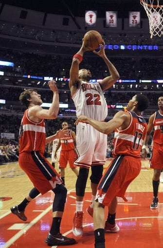 Apr 17, 2013; Chicago, IL, USA;  Chicago Bulls power forward Taj Gibson (22)  shoots over Washington Wizards small forward Jan Vesely (24) and guard Garrett Temple (17)at the United Center. Mandatory Credit: David Banks-USA TODAY Sports