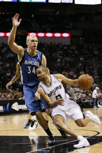 Apr 17, 2013; San Antonio, TX, USA; San Antonio Spurs guard Tony Parker (9) drives to the basket while guarded by Minnesota Timberwolves  center Greg Stiemsma (34) during the first half at the AT&T Center. Mandatory Credit: Soobum Im-USA TODAY Sports