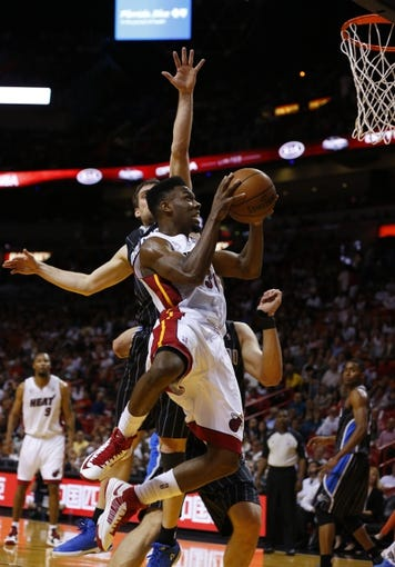 Apr 17, 2013; Miami, FL, USA;  Miami Heat point guard Norris Cole (30) drives to the basket as Orlando Magic point guard Beno Udrih defends in the second half at the American Airlines Arena. The Heat won 105-93.  Mandatory Credit: Robert Mayer-USA TODAY Sports
