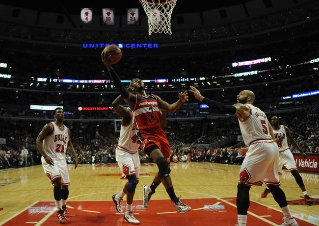 Apr 17, 2013; Chicago, IL, USA;  Washington Wizards point guard John Wall (2) is defended by Chicago Bulls power forward Carlos Boozer (5) during the second half at the United Center. The Chicago Bulls defeated the Washington Wizards 95-92. Mandatory Credit: David Banks-USA TODAY Sports