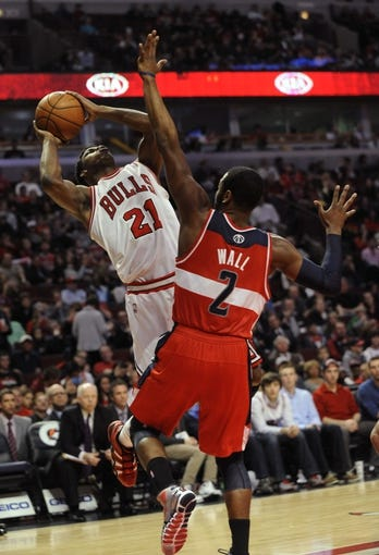 Apr 17, 2013; Chicago, IL, USA;  Chicago Bulls small forward Jimmy Butler (21) is defended by Washington Wizards point guard John Wall (2) during the second half at the United Center. The Chicago Bulls defeated the Washington Wizards 95-92. Mandatory Credit: David Banks-USA TODAY Sports