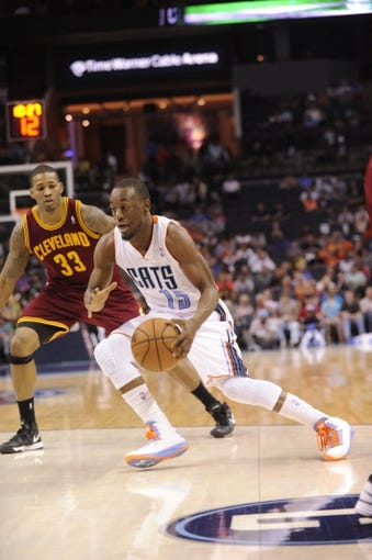 April 17, 2013; Charlotte, NC, USA; Charlotte Bobcats guard Kemba Walker (15) drives into the paint as he is defended by Cleveland Cavaliers forward Alonzo Gee (33)  during the game at Time Warner Cable Arena. Bobcats win 105-98. Mandatory Credit: Sam Sharpe-USA TODAY Sports