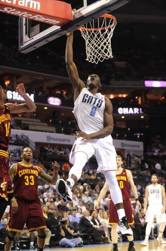 April 17, 2013; Charlotte, NC, USA; Charlotte Bobcats forward center Bismack Biyombo (0) drives to the basket and dunks the ball during the game against the Cleveland Cavaliers at Time Warner Cable Arena. Bobcats win 105-98. Mandatory Credit: Sam Sharpe-USA TODAY Sports