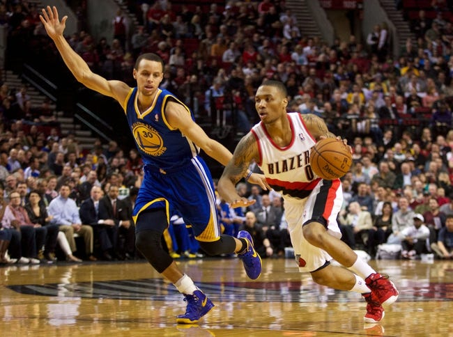 April 17, 2013; Portland, OR, USA; Portland Trail Blazers point guard Damian Lillard (0) dribbles past Golden State Warriors point guard Stephen Curry (30) in the first half at the Rose Garden.  Mandatory Credit: Jaime Valdez-USA TODAY Sports