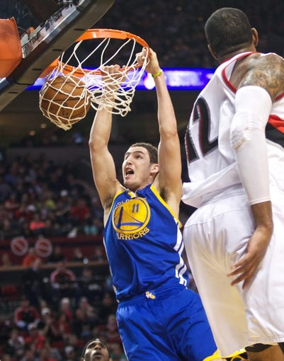 April 17, 2013; Portland, OR, USA; Golden State Warriors shooting guard Klay Thompson (11) dunks the ball past Portland Trail Blazers power forward LaMarcus Aldridge (12) in the second half at the Rose Garden.  Mandatory Credit: Jaime Valdez-USA TODAY Sports