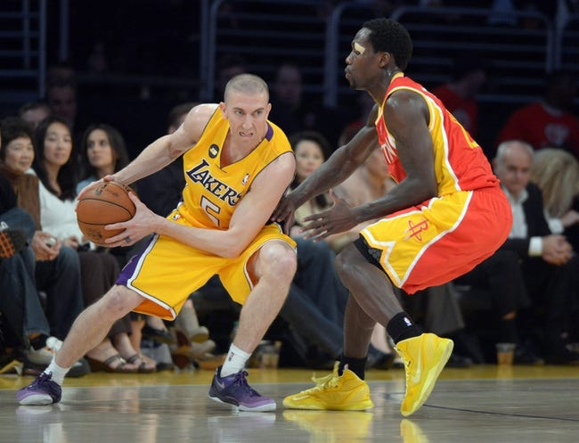 Apr 17, 2013; Los Angeles, CA, USA; Los Angeles Lakers guard Steve Blake (5) is defended by Houston Rockets guard Patrick Beverly (12) at the Staples Center. The Lakers defeated the Rockets 99-95 in overtime. Mandatory Credit: Kirby Lee-USA TODAY Sports