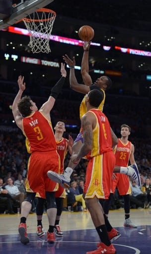 Apr 17, 2013; Los Angeles, CA, USA; Los Angeles Lakers center Dwight Howard (12) is defended by Houston Rockets forward Greg Smith (4) and center Omer Asik (3) at the Staples Center. The Lakers defeated the Rockets 99-95 in overtime. Mandatory Credit: Kirby Lee-USA TODAY Sports