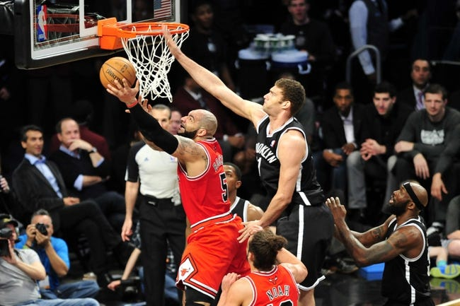 Apr 20, 2013; Brooklyn, NY, USA; Chicago Bulls power forward Carlos Boozer (5) puts up a layup over Brooklyn Nets center Brook Lopez (11) during the second half of game one of the first round of the 2013 NBA Playoffs at the Barclays Center. The Nets won the game 106-89. Mandatory Credit: Joe Camporeale-USA TODAY Sports