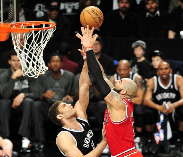 Apr 20, 2013; Brooklyn, NY, USA; Chicago Bulls power forward Carlos Boozer (5) attempts a shot over Brooklyn Nets center Brook Lopez (11) during the second half of game one of the first round of the 2013 NBA Playoffs at the Barclays Center. The Nets won the game 106-89. Mandatory Credit: Joe Camporeale-USA TODAY Sports
