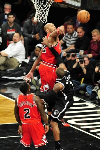 Apr 20, 2013; Brooklyn, NY, USA; Chicago Bulls power forward Taj Gibson (22) rejects a shot by Brooklyn Nets point guard C.J. Watson (1) during the second half of game one of the first round of the 2013 NBA Playoffs at the Barclays Center. The Nets won the game 106-89. Mandatory Credit: Joe Camporeale-USA TODAY Sports