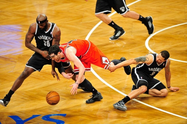 Apr 20, 2013; Brooklyn, NY, USA; Brooklyn Nets power forward Reggie Evans (30) and Chicago Bulls shooting guard Kirk Hinrich (12) and Brooklyn Nets point guard Deron Williams (8) go after a loose ball during the second half of game one of the first round of the 2013 NBA Playoffs at the Barclays Center. The Nets won the game 106-89. Mandatory Credit: Joe Camporeale-USA TODAY Sports