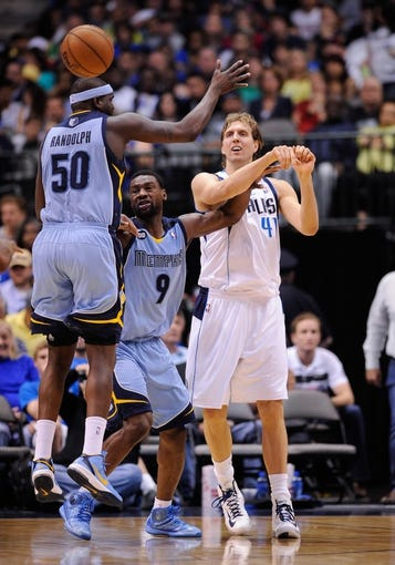 Apr 15, 2013; Dallas, TX, USA; Dallas Mavericks power forward Dirk Nowitzki (41) passes the ball around Memphis Grizzlies shooting guard Tony Allen (9) and power forward Zach Randolph (50) during the game at the American Airlines Center. Mandatory Credit: Jerome Miron-USA TODAY Sports