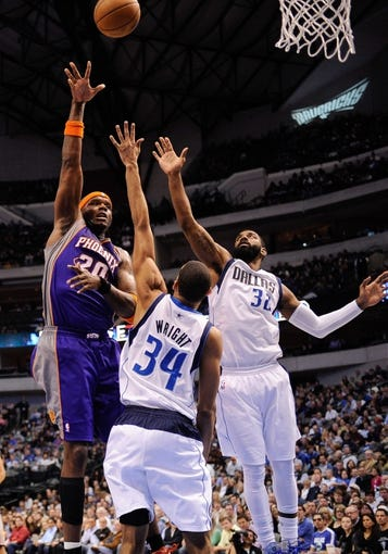 Apr 10, 2013; Dallas, TX, USA; Phoenix Suns center Jermaine O'Neal (20) shoots the ball over Dallas Mavericks center Brandan Wright (34) and shooting guard O.J. Mayo (32) at the American Airlines Center. The Suns defeated the Mavericks 102-91. Mandatory Credit: Jerome Miron-USA TODAY Sports