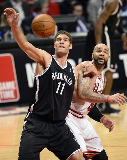 Apr 25, 2013; Chicago, IL, USA; Brooklyn Nets center Brook Lopez (11) grabs a rebound over Chicago Bulls power forward Carlos Boozer (5) in the second half during game three of the first round of the 2013 NBA playoffs at the United Center. Chicago defeats Brooklyn 79-76. Mandatory Credit: Mike DiNovo-USA TODAY Sports