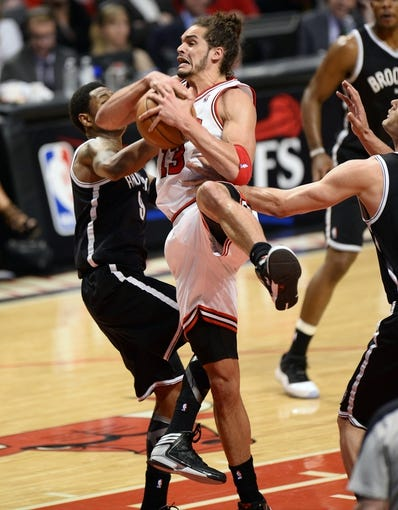 Apr 25, 2013; Chicago, IL, USA;  Chicago Bulls center Joakim Noah (13) rebounds the ball against Brooklyn Nets shooting guard MarShon Brooks (9) in the second half during game three of the first round of the 2013 NBA playoffs at the United Center. Chicago defeats Brooklyn 79-76. Mandatory Credit: Mike DiNovo-USA TODAY Sports