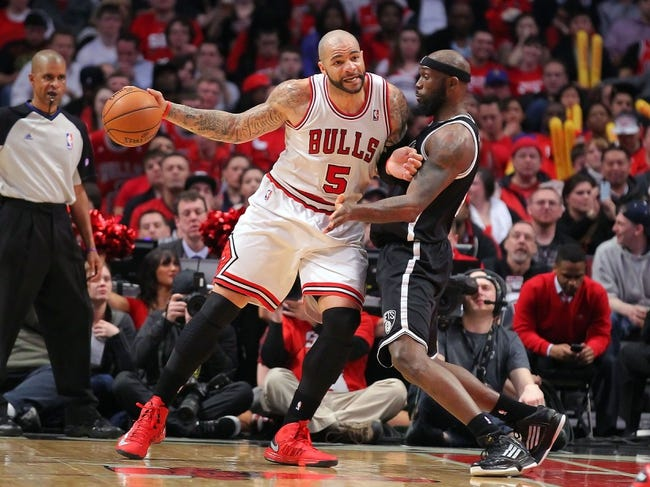 Apr 25, 2013; Chicago, IL, USA; Chicago Bulls power forward Carlos Boozer (5) is defended by Brooklyn Nets power forward Reggie Evans (30) during the second half of game three of the first round of the 2013 NBA playoffs at the United Center. Chicago won 79-76. Mandatory Credit: Dennis Wierzbicki-USA TODAY Sports