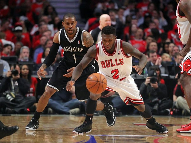 Apr 25, 2013; Chicago, IL, USA; Brooklyn Nets point guard C.J. Watson (1) and Chicago Bulls point guard Nate Robinson (2) battle for the ball during the second half of game three of the first round of the 2013 NBA playoffs at the United Center. Chicago won 79-76. Mandatory Credit: Dennis Wierzbicki-USA TODAY Sports