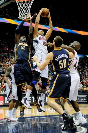 Apr 27, 2013; Atlanta, GA, USA; Atlanta Hawks center Al Horford (15) grabs a rebound above Indiana Pacers center Roy Hibbert (55) during the second half of game three of the first round of the 2013 NBA playoffs at Philips Arena. The Hawks defeated the Pacers, 90-69. Mandatory Credit: Dale Zanine-USA TODAY Sports