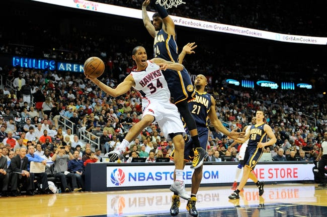 Apr 27, 2013; Atlanta, GA, USA; Atlanta Hawks point guard Devin Harris (34) passes the ball around Indiana Pacers small forward Paul George (24) during the first half during game three in the first round of the 2013 NBA playoffs at Philips Arena.The Hawks defeated the Pacers 90-69. Mandatory Credit: Dale Zanine-USA TODAY Sports