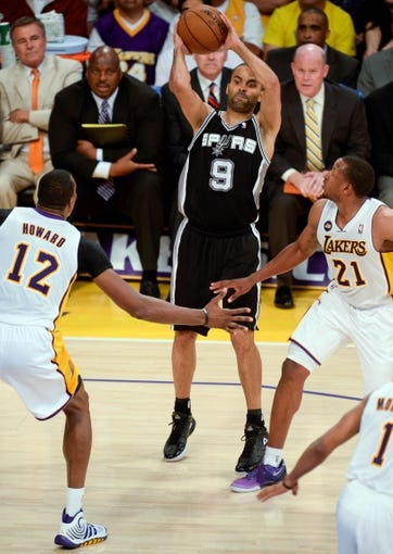 Apr 28, 2013; Los Angeles, CA, USA; San Antonio Spurs point guard Tony Parker (9) leaps as he throws a pass between Los Angeles Lakers center Dwight Howard (12) and guard Chris Duhon (21) in first half action in game four of the first round of the 2013 NBA playoffs at the Staples Center. Mandatory Credit: Robert Hanashiro-USA TODAY Sports