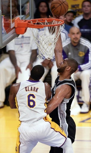Apr 28, 2013; Los Angeles, CA, USA; San Antonio Spurs power forward Tim Duncan (21) scores past Los Angeles Lakers small forward Earl Clark (6) during 1st half action in game four of the first round of the 2013 NBA playoffs at the Staples Center. Mandatory Credit: Robert Hanashiro-USA TODAY Sports