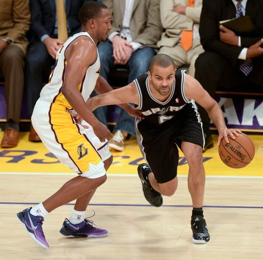 Apr 28, 2013; Los Angeles, CA, USA; San Antonio Spurs point guard Tony Parker (9) dribbles past Los Angeles Lakers point guard Chris Duhon (21) during second half action  in game four of the first round of the 2013 NBA playoffs at the Staples Center. The Spurs won 103-82 and eliminated the Lakers. Mandatory Credit: Robert Hanashiro-USA TODAY Sports