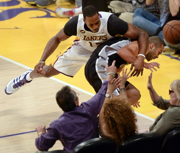 Apr 28, 2013; Los Angeles, CA, USA; Los Angeles Lakers center Dwight Howard (12) and the Spurs Tony Parker collide as they chase a loose ball to the sidelines during game four of the first round of the 2013 NBA playoffs at the Staples Center. The Spurs won 103-82 and eliminated the Lakers. Mandatory Credit: Robert Hanashiro, USA TODAY sports