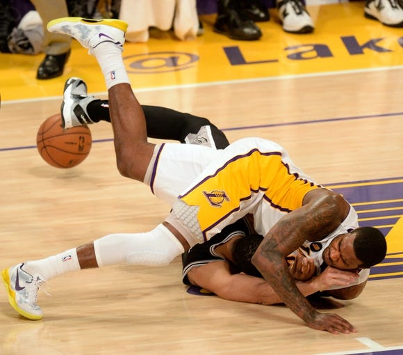 Apr 28, 2013; Los Angeles, CA, USA; Los Angeles Lakers small forward Earl Clark (6) and San Antonio Spurs shooting guard Danny Green (4) collide while chasing down a loose ball during 2nd quarter action of game four of the first round of the 2013 NBA playoffs at the Staples Center. Mandatory Credit: Robert Hanashiro-USA TODAY Sports