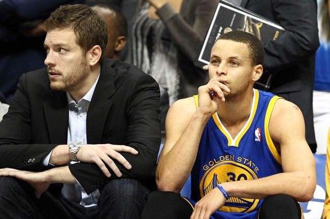 Apr 30, 2013; Denver, CO, USA; Golden State Warriors point guard Stephen Curry (30) sits next to an injured power forward David Lee (left) in the fourth quarter against the Denver Nuggets in game five of the first round of the 2013 NBA Playoffs at the Pepsi Center. The Nuggets won 107-100. Mandatory Credit: Isaiah J. Downing-USA TODAY Sports